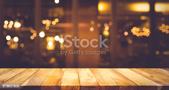 864907996istockphoto Wood table with blur light bokeh in dark night cafe 879637826