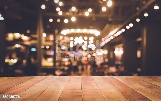 864907996istockphoto Wood table with blur light bokeh in dark night cafe 880436778