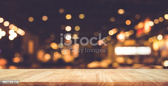 864907996istockphoto Wood table with blur light bokeh in dark night cafe 882789158