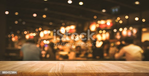 864907996istockphoto Wood table with blur light bokeh in dark night cafe 885452994