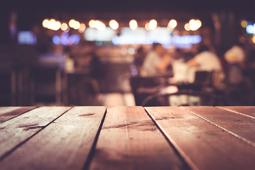 Wood table with blur light in night cafe,restaurant background