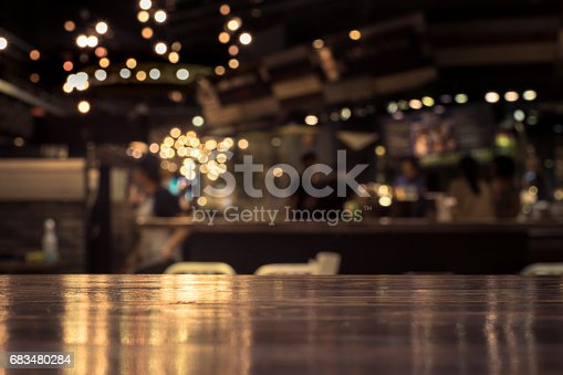 Wood table top with reflect on blur of lighting in night cafe,restaurant background/selective focus.Wood table top with blur light bokeh in dark night cafe,restaurant background .Lifestyle and celebration concepts