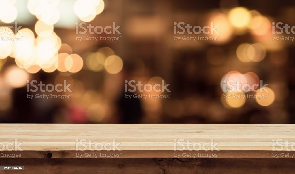 Wood table with blur light in night cafe,restaurant background stock photo