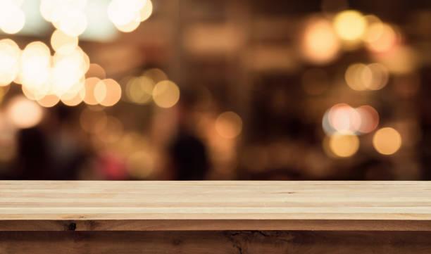 holztisch mit licht im nachtcafé, restaurant hintergrund unschärfe - goldene bar stock-fotos und bilder