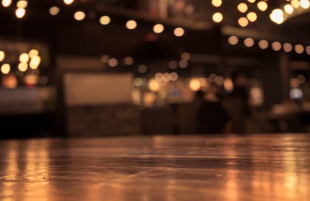 holztisch mit licht im nachtcafé, restaurant hintergrund unschärfe - tresentisch stock-fotos und bilder