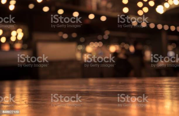 Photo of Wood table with blur light in night cafe,restaurant background