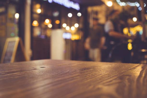 holztisch mit unschärfe der beleuchtung in der nacht-café-bereich - goldene bar stock-fotos und bilder