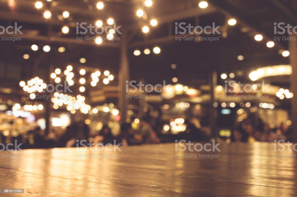 Wood table with blur of lighting in night cafe - foto stock