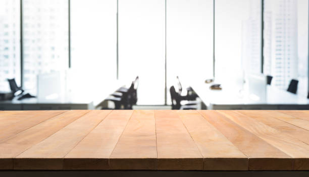 wood table with blur room office and window city view - office desk stock photos and pictures