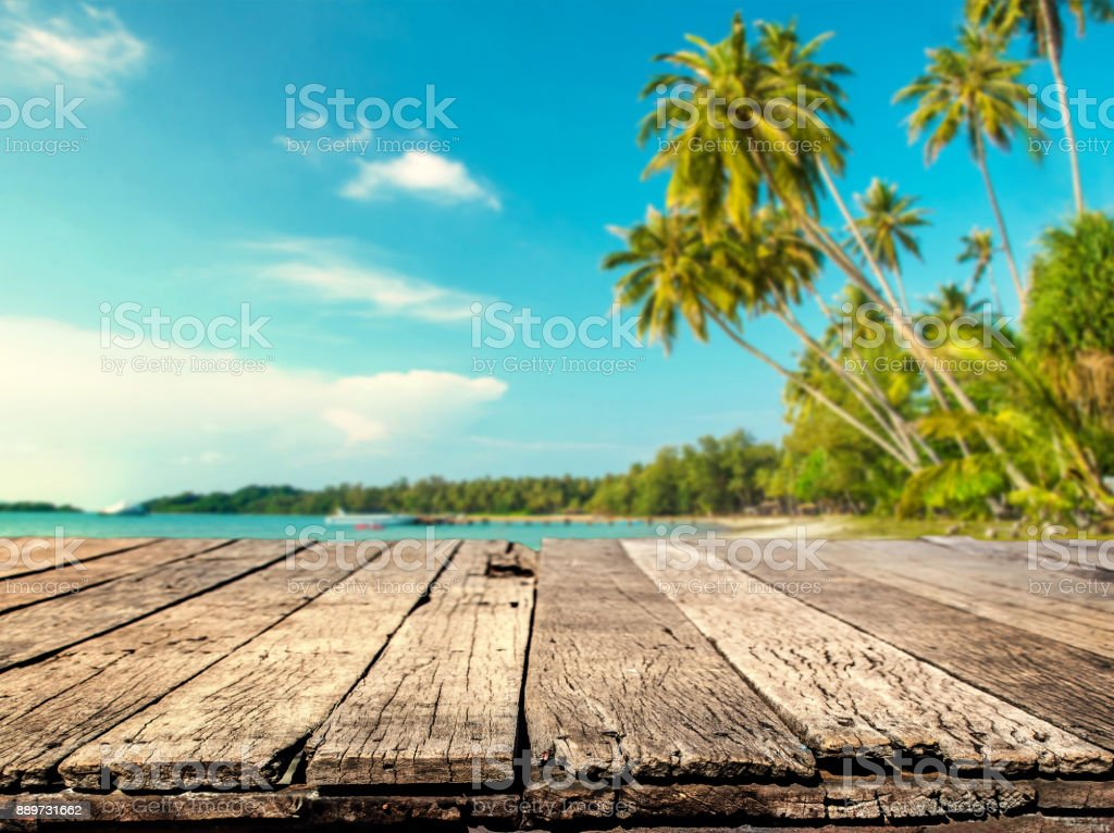 Wood table with blurred sea and coconut tree background stock photo