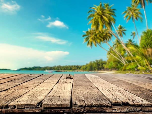 Holztisch mit Meer und Kokosnuss Baum der Hintergrund jedoch unscharf – Foto