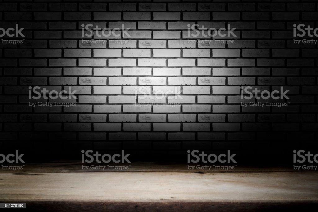 Wood table with dark brick wall blurred background for present product. stock photo