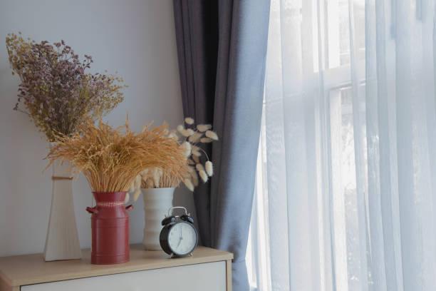 holztisch mit dekorblumen auf weißem vorhang-fensterstruktur hintergrund. - fensterdeko herbst stock-fotos und bilder