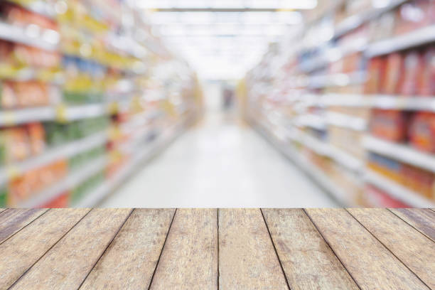 Wood table with Empty Supermarket aisle shelves abstract blur defocused business background stock photo