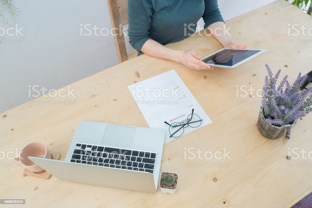 wood table with human hand hold smartphone, tablet, cell phone with resume information, laptop and purple lavender flower on pot. concept of job search online. photo libre de droits