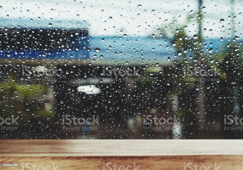 Wood Table with Raindrop on Window in Rainy Day, for background stock photo