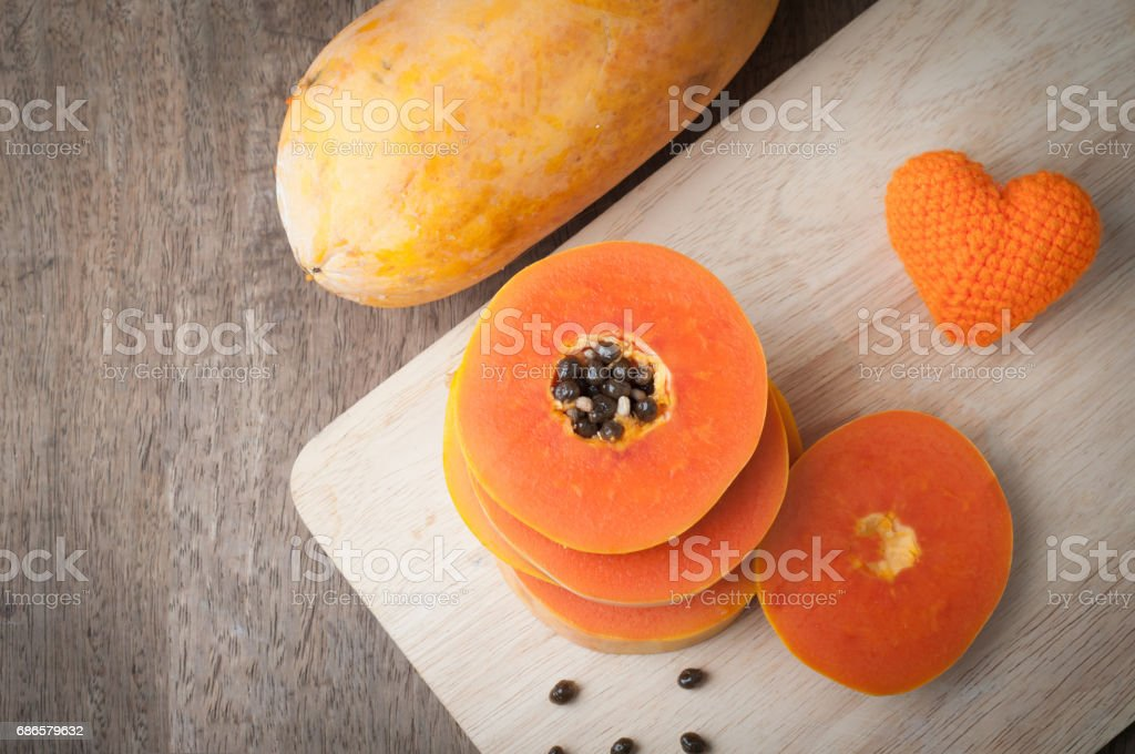 wood table with slice ripe papaya and orange heart shape sign on wood cutting board - healthy eating and dieting food, concept of health care. foto stock royalty-free