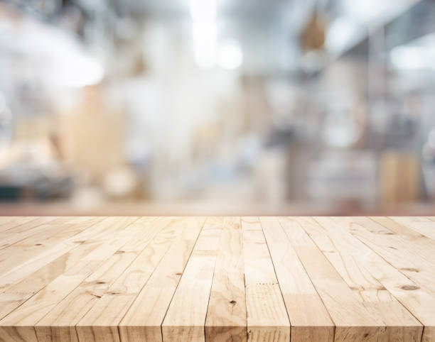 Wood table,counter island on blur kitchen room background.For montage product display or design key visual stock photo