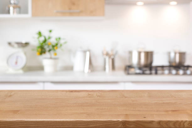 Wood tabletop on blur kitchen counter background for product display Wood tabletop on blur kitchen counter background for product display kitchen counter stock pictures, royalty-free photos & images