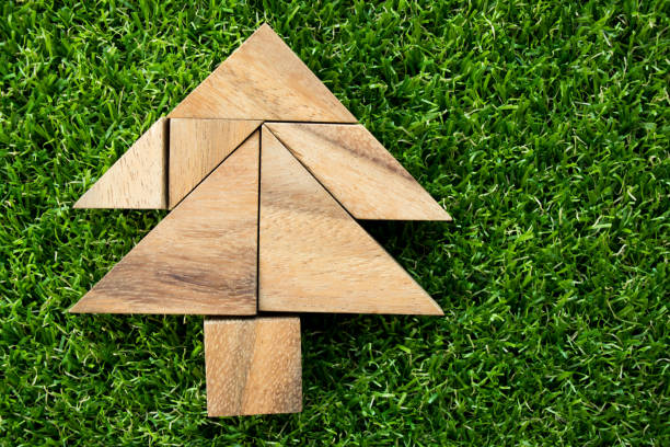 wood tangram puzzle in christmas tree shape on artificial green grass background - tree logo stock photos and pictures