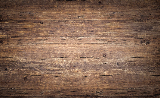 Wood texture background. Top view of vintage wooden table with cracks. Brown rustic rough timber for backdrop. Surface of old knotted wood with natural color, texture and pattern. Dark barn material.