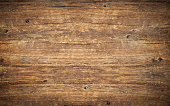 Wood texture background. Top view of vintage wooden table with cracks. Surface of old knotted wood with natural color, texture and pattern. Dark barn material. Brown rustic rough timber for backdrop.
