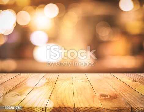 864907996istockphoto Wood texture table top (counter bar) with blur light gold bokeh background 1199391780