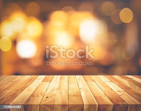 924418708 istock photo Wood texture table top (counter bar) with blur light gold bokeh background 1208843482