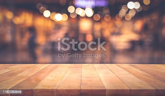 864907996istockphoto Wood texture table top (counter bar) with blur light gold bokeh in cafe,restaurant background 1162090949