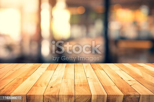 924418708 istock photo Wood texture table top (counter bar) with blur light gold bokeh in cafe,restaurant background 1163099272
