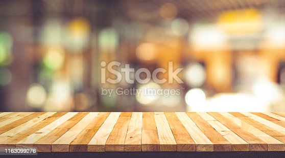 924418708 istock photo Wood texture table top (counter bar) with blur light gold bokeh in cafe,restaurant background 1163099276