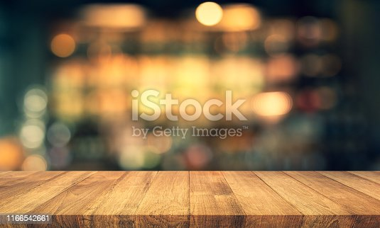 istock Wood texture table top (counter bar) with blur light gold bokeh in cafe,restaurant background 1166542661