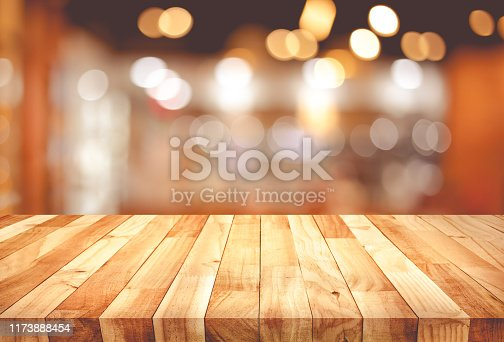 864907996istockphoto Wood texture table top (counter bar) with blur light gold bokeh in cafe,restaurant background 1173888454