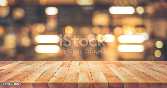 864907996istockphoto Wood texture table top (counter bar) with blur light gold bokeh in cafe,restaurant background 1179621653