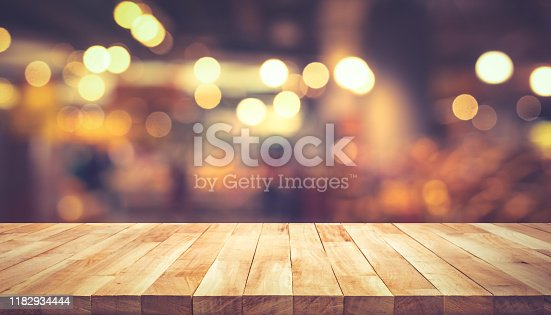 924418708 istock photo Wood texture table top (counter bar) with blur light gold bokeh in cafe,restaurant background 1182934444