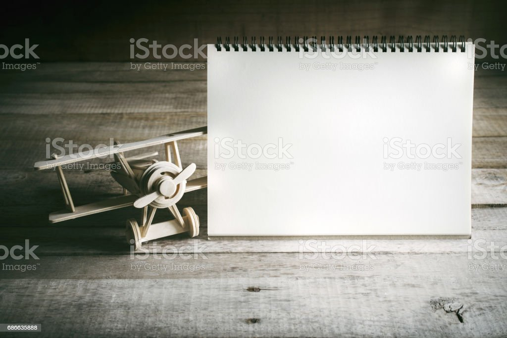 wood toy airplane with blank notebook on wood table with copy space ready for your design. royalty-free stock photo