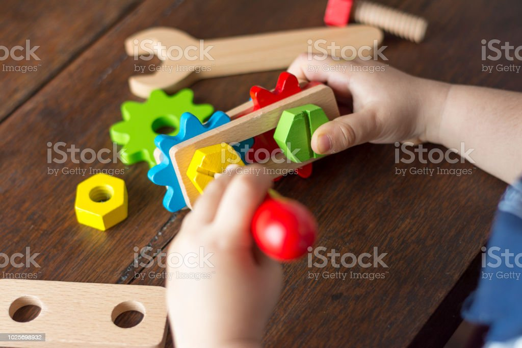 Close-up of the hands of a child playing with wooden toolkits.