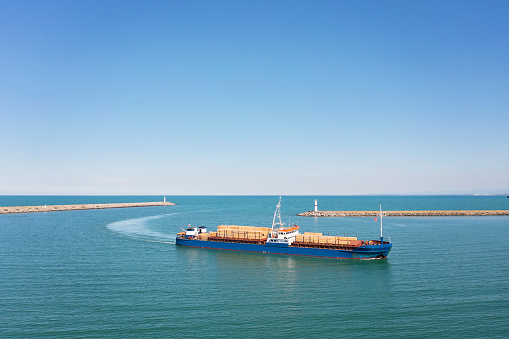 Aerial view of small cargo ship approaching to the port.