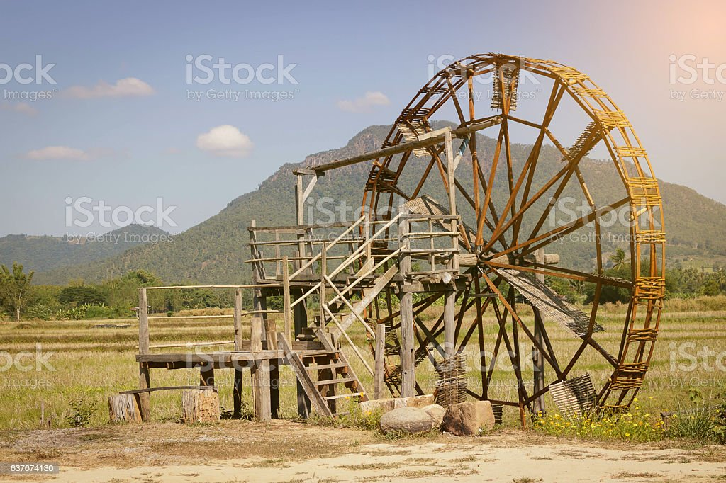 Wood turbine beside rice field. stock photo
