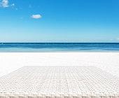 Wood weave table surface with sunny beach background
