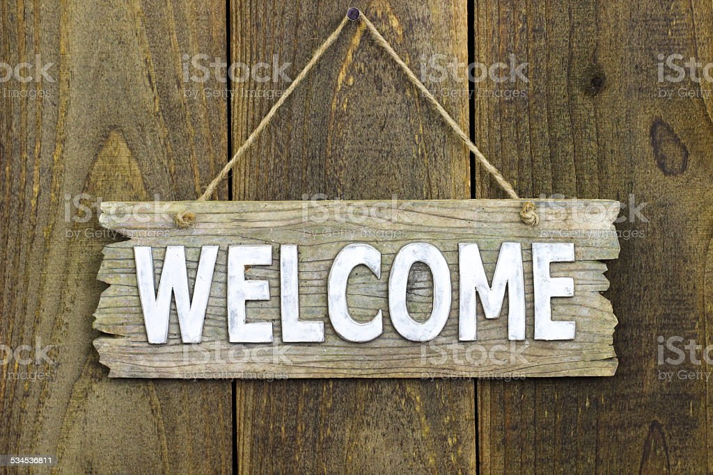 Wood welcome sign hanging on wooden door stock photo