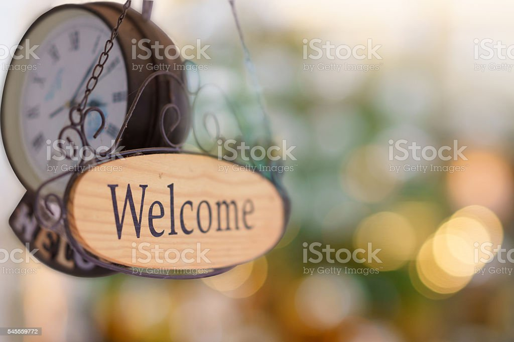 Wood welcome sign hanging with wall clock. selective focus stock photo