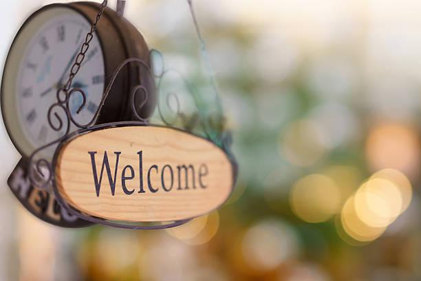 wood welcome sign hanging with wall clock. selective focus - uhrenshop stock-fotos und bilder