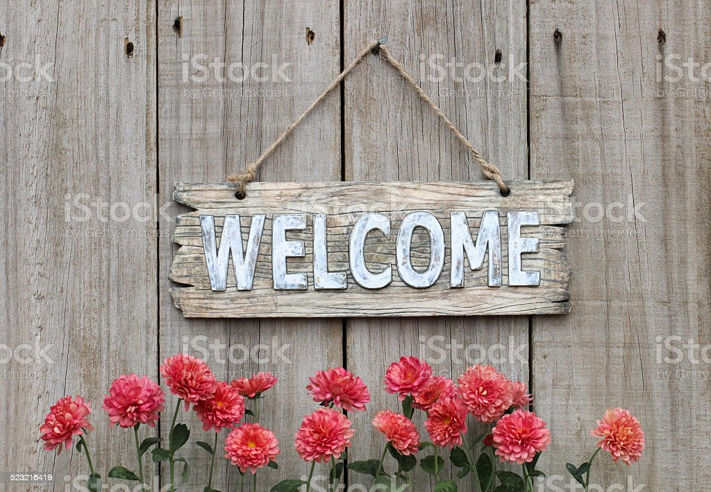 Wood welcome sign with autumn flower border by wooden background stock photo