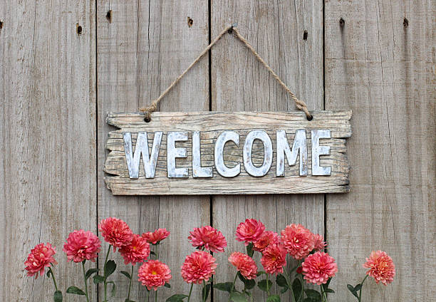 wood welcome sign with autumn flower border by wooden background - welcome stock photos and pictures