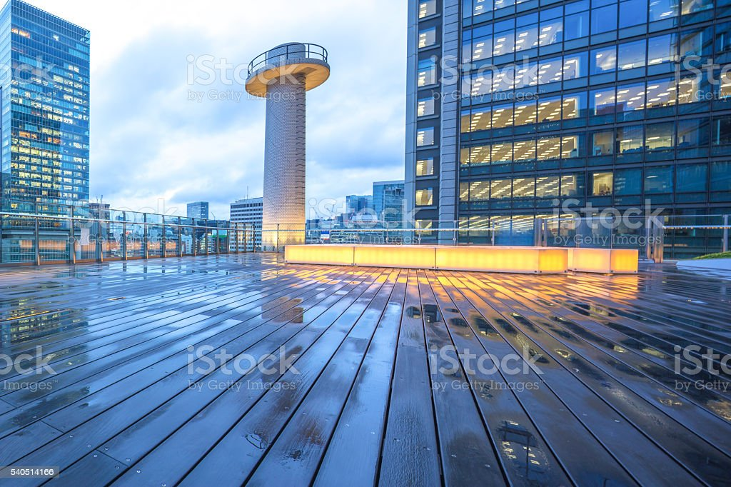Bois sol mouillé un immeuble de bureaux moderne au crépuscule à