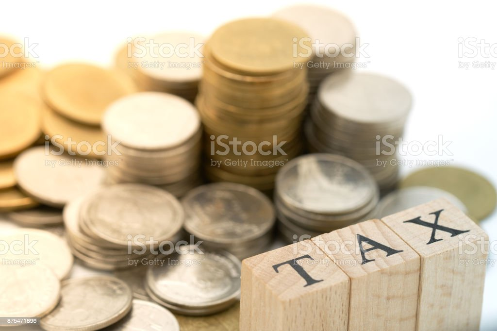 Wood Word Tax Placed On Pile Of Coins As Background Business Concept