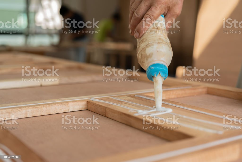 wood work carpenter concept with close up hand use glue for work