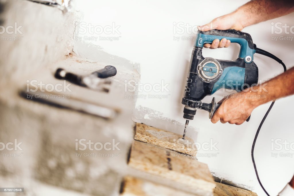wood worker using professional drill press for making holes in wood boards and concrete stock photo