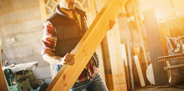 Wood working. Closeup of a carpenter carrying thick wooden plank inside of a bit dusty old school workshop, lit with low sunlight on the sides. The man is partially unrecognizable. lumberjack stock pictures, royalty-free photos & images